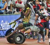 En pleno festejo el jamaiquino Usaín Bolt fue derribado por un camarógrafo que perdió el control al caerse del carro en el que se desplazaba con la cámara.
