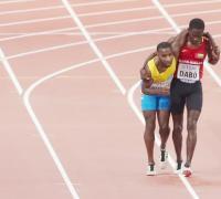 Espíritu deportivo: Braima Dabo, de Guinea-Bissau,  ayuda  al exhausto Aruban Johnathan Busby a cruzar la línea de meta de  los 5.000 metros
