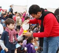 Juan Carlos Argüello siriviendo el refrigerio a uno de los niños