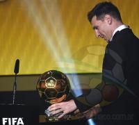 Leo Messi mira con cariño su quinto balón de oro